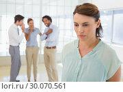 Купить «Colleauges gossiping with sad businesswoman in foreground», фото № 30070561, снято 19 декабря 2013 г. (c) Wavebreak Media / Фотобанк Лори