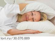 Купить «Irritated woman covering ears with pillows», фото № 30070889, снято 18 декабря 2013 г. (c) Wavebreak Media / Фотобанк Лори