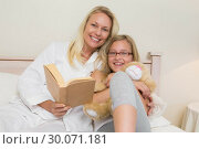Купить «Happy mother and daughter with novel in bed», фото № 30071181, снято 18 декабря 2013 г. (c) Wavebreak Media / Фотобанк Лори