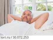 Купить «Relaxed mature man lying in bed at home», фото № 30072253, снято 6 декабря 2013 г. (c) Wavebreak Media / Фотобанк Лори