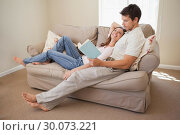 Купить «Relaxed young couple reading book on couch», фото № 30073221, снято 12 декабря 2013 г. (c) Wavebreak Media / Фотобанк Лори