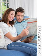 Relaxed couple reading newspaper on couch. Стоковое фото, агентство Wavebreak Media / Фотобанк Лори