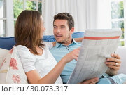 Relaxed happy couple reading newspaper on couch. Стоковое фото, агентство Wavebreak Media / Фотобанк Лори