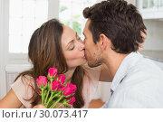 Купить «Loving couple kissing with flowers in hand at home», фото № 30073417, снято 12 декабря 2013 г. (c) Wavebreak Media / Фотобанк Лори