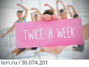 Купить «Woman holding pink card saying twice a week», фото № 30074201, снято 21 марта 2014 г. (c) Wavebreak Media / Фотобанк Лори