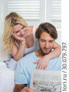 Happy casual couple sitting on couch reading newspaper together. Стоковое фото, агентство Wavebreak Media / Фотобанк Лори