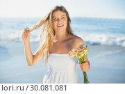 Beautiful blonde in sundress holding roses on the beach. Стоковое фото, агентство Wavebreak Media / Фотобанк Лори