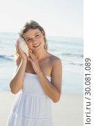 Beautiful blonde in white sundress on the beach listening to conch. Стоковое фото, агентство Wavebreak Media / Фотобанк Лори