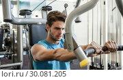 Купить «Focused man using weights machine for arms», фото № 30081205, снято 26 февраля 2014 г. (c) Wavebreak Media / Фотобанк Лори