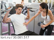 Fit man using weights machine for arms with his trainer. Стоковое фото, агентство Wavebreak Media / Фотобанк Лори