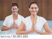 Купить «Smiling couple in white sitting in lotus pose with hands together», фото № 30081685, снято 9 апреля 2014 г. (c) Wavebreak Media / Фотобанк Лори