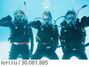 Купить «Friends on scuba training submerged in swimming pool showing thumbs down», фото № 30081885, снято 9 апреля 2014 г. (c) Wavebreak Media / Фотобанк Лори