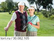 Купить «Golfing couple smiling at camera», фото № 30082105, снято 3 апреля 2014 г. (c) Wavebreak Media / Фотобанк Лори