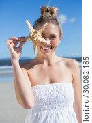Купить «Pretty blonde in white dress holding starfish on the beach », фото № 30082185, снято 3 апреля 2014 г. (c) Wavebreak Media / Фотобанк Лори