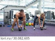 Купить «Bodybuilding man and woman lifting kettlebells in a squat », фото № 30082605, снято 2 апреля 2014 г. (c) Wavebreak Media / Фотобанк Лори