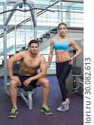 Купить «Bodybuilding man and woman posing for the camera», фото № 30082613, снято 2 апреля 2014 г. (c) Wavebreak Media / Фотобанк Лори