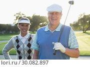 Купить «Golfing couple smiling at camera», фото № 30082897, снято 3 апреля 2014 г. (c) Wavebreak Media / Фотобанк Лори