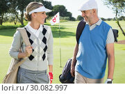 Купить «Golfing couple walking away from eighteenth hole», фото № 30082997, снято 3 апреля 2014 г. (c) Wavebreak Media / Фотобанк Лори