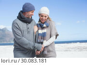 Купить «Smiling couple standing on the beach in warm clothing», фото № 30083181, снято 3 апреля 2014 г. (c) Wavebreak Media / Фотобанк Лори