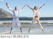 Купить «Happy couple jumping on the beach together», фото № 30083313, снято 3 апреля 2014 г. (c) Wavebreak Media / Фотобанк Лори