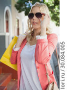 Купить «Pretty blonde in sunglasses holding shopping bags», фото № 30084005, снято 19 февраля 2014 г. (c) Wavebreak Media / Фотобанк Лори