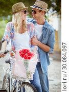 Купить «Hip young couple going for a bike ride», фото № 30084097, снято 19 февраля 2014 г. (c) Wavebreak Media / Фотобанк Лори