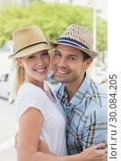 Купить «Young hip couple hugging and smiling at camera», фото № 30084205, снято 19 февраля 2014 г. (c) Wavebreak Media / Фотобанк Лори