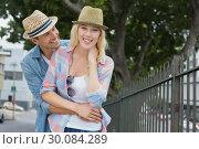 Купить «Hip young couple smiling at camera by railings», фото № 30084289, снято 19 февраля 2014 г. (c) Wavebreak Media / Фотобанк Лори