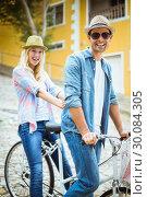 Купить «Hip young couple going for a bike ride», фото № 30084305, снято 19 февраля 2014 г. (c) Wavebreak Media / Фотобанк Лори