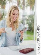 Купить «Pretty blonde sitting at table having coffee sending text», фото № 30084405, снято 19 февраля 2014 г. (c) Wavebreak Media / Фотобанк Лори