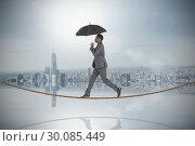 Купить «Composite image of businessman walking and holding umbrella on tightrope», фото № 30085449, снято 11 июня 2014 г. (c) Wavebreak Media / Фотобанк Лори