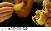 Closeup of man with burger and fries. Стоковое видео, видеограф Ekaterina Demidova / Фотобанк Лори