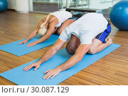 Купить «Couple in bending posture at fitness studio», фото № 30087129, снято 27 февраля 2014 г. (c) Wavebreak Media / Фотобанк Лори