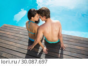 Купить «Romantic young couple by swimming pool», фото № 30087697, снято 8 апреля 2014 г. (c) Wavebreak Media / Фотобанк Лори