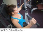 Купить «Fit brunette using weights machine for arms», фото № 30088353, снято 5 марта 2014 г. (c) Wavebreak Media / Фотобанк Лори