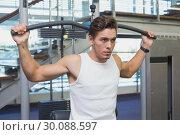 Купить «Strong man using weights machine for arms», фото № 30088597, снято 5 марта 2014 г. (c) Wavebreak Media / Фотобанк Лори
