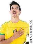 Brazilian football player in yellow singing to anthem. Стоковое фото, агентство Wavebreak Media / Фотобанк Лори