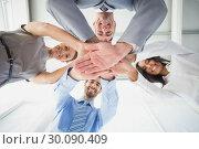 Купить «Four workers stacking hands together», фото № 30090409, снято 6 мая 2014 г. (c) Wavebreak Media / Фотобанк Лори