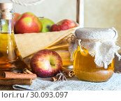 Купить «Processing of an agricultural crop of red and green apples. Home canning, healthy diet vegetarian food. Spiced apple cider vinegar, juice, cinnamon cider in a glass jar next to a box of ripe fruit», фото № 30093097, снято 16 февраля 2019 г. (c) Светлана Евграфова / Фотобанк Лори