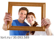 Купить «Couple holding frame ahead of them», фото № 30093589, снято 4 июля 2014 г. (c) Wavebreak Media / Фотобанк Лори
