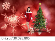 Composite image of pretty girl smiling in santa outfit . Стоковое фото, агентство Wavebreak Media / Фотобанк Лори