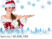 Composite image of pretty redhead in santa outfit presenting with hands. Стоковое фото, агентство Wavebreak Media / Фотобанк Лори