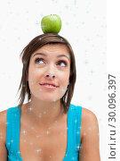 Купить «Composite image of attractive young woman standing upright with a green apple on her head», фото № 30096397, снято 29 августа 2014 г. (c) Wavebreak Media / Фотобанк Лори