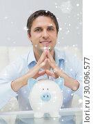 Купить «Composite image of handsome casual man with piggy bank in living room», фото № 30096577, снято 29 августа 2014 г. (c) Wavebreak Media / Фотобанк Лори