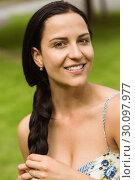 Купить «Portrait of a pretty brunette holding her braid», фото № 30097977, снято 20 июня 2014 г. (c) Wavebreak Media / Фотобанк Лори