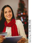Купить «Pretty brunette shopping online with tablet at christmas», фото № 30098709, снято 24 июля 2014 г. (c) Wavebreak Media / Фотобанк Лори