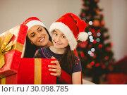 Купить «Festive mother and daughter opening a christmas gift», фото № 30098785, снято 24 июля 2014 г. (c) Wavebreak Media / Фотобанк Лори