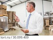 Купить «Warehouse boss checking his inventor», фото № 30099409, снято 6 сентября 2014 г. (c) Wavebreak Media / Фотобанк Лори
