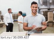 Купить «Manager looking at camera while holding clipboard», фото № 30099437, снято 6 сентября 2014 г. (c) Wavebreak Media / Фотобанк Лори