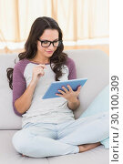 Купить «Pretty brunette using her tablet», фото № 30100309, снято 2 октября 2014 г. (c) Wavebreak Media / Фотобанк Лори